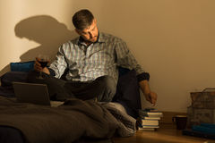 Lonely man smoking in bed Royalty Free Stock Photography