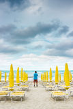 Lonely man is standing on the empty beach and looking out to the Royalty Free Stock Image