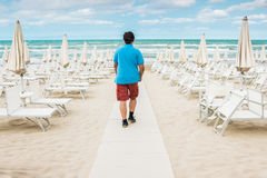 Lonely man is standing on the empty beach and looking out to the Stock Images