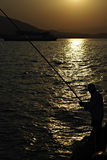 Fisherman. Lonely man standing at seashore and fishing with fishing rod against sun reflection on water at summer sunset Royalty Free Stock Photos