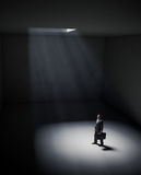 A lonely man standing in a spot of light Royalty Free Stock Images