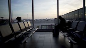 Lonely man with suitcase waiting for plane at the departure lounge, terminal. Stock footage stock footage