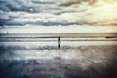 Lonely man walking on a beach. Lonely man walking on the beach on a rainy day on Hendaye beach in Pays Basque, France royalty free stock image