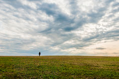 A lonely man walking on the horizon of the landscape Stock Photography