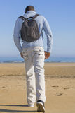 Lonely man walking toward the sea, seen from the back Stock Images