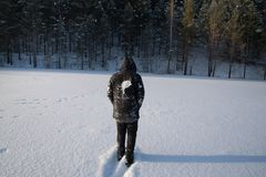 A lonely man walks in the snow. Dramatic silhouette of a man walking in a snowy clearing in the forest. Coldly. A man walking in the snow stock photos