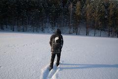 A lonely man walks in the snow. Dramatic silhouette of a man walking in a snowy clearing in the forest. Coldly. A man walking in the snow stock images