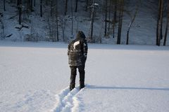 A lonely man walks in the snow. Dramatic silhouette of a man walking in a snowy clearing in the forest. Coldly. A man walking in the snow royalty free stock image