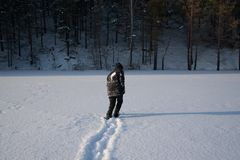 A lonely man walks in the snow. Dramatic silhouette of a man walking in a snowy clearing in the forest. Coldly. A man walking in the snow royalty free stock photography