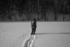 A lonely man walks in the snow. Dramatic silhouette of a man walking in a snowy clearing in the forest. Coldly. A man walking in the snow. black and white stock images