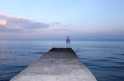 Lonely man watching the sunset on the pier Royalty Free Stock Photography