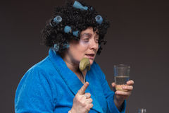 Lonely mature fat woman alcoholic drinks vodka from glasses and Stock Photos