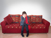 Lonely mature woman on large empty sofa, sad. Stock Image