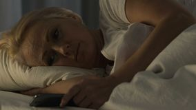 Lonely mature woman lying in bed and viewing family photo on cellphone, insomnia. Stock footage stock video