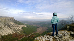 Lonely Mature woman standing on edge of cliff and looks at view. Dressed in a jacket and jeans. The view from the back. Royalty Free Stock Image