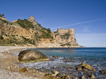 Lonely Mediterranean Beach. Beautiful Mediterranean cove located in the Costa Blanca of Spain, with some rocks on the foreground Stock Image