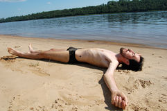 Lonely Men lying on the beach. Beautiful lonely men lying on the beach, totally relaxed Royalty Free Stock Photography