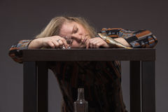 Lonely middle-aged woman drinks some vodka sadness alcohol and e Stock Image