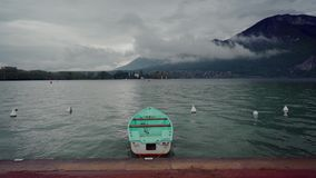 Lonely mint boat moored to promenade of Lake Annecy on fog mountains background in rainy day. 4k stock video