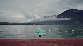 Lonely mint boat moored to promenade of Lake Annecy on fog mountains background in rainy day. 4k stock video footage
