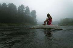 Lonely in the Mist. Reclusive Girl is Sitting alone on the Rock in the Middle of the River During an Early Morning Mist