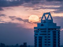 The lonely moment from a friendless guy looking at an abandoned. Building with giant moon behind. This is an supermoon phenomenon day in Bangkok city of Royalty Free Stock Images