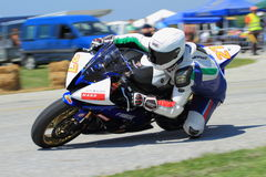Lonely motorbike racer in the left turn on the track. Lonely motorbike racer on the track. Blurred background stock images