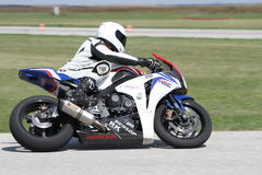 Lonely motorbike racer in the left turn on the track. Blurred background stock image