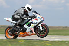 Lonely motorbike racer on the track raised on rear wheel. Stock Image