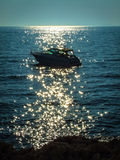 A lonely motorboat in the sea. With sun reflection on the water stock images
