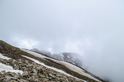 A lonely mountain. A mountain covered in clouds at high altitude Stock Photo