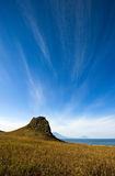 Lonely mountain under a blue sky on the coast. Stock Photography
