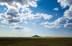 Lonely mountain in yellow steppe under beautiful sky with white fluffy clouds, central Kazakhstan Stock Photography