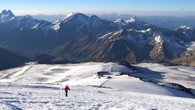 Lonely mountaineer in crampons coming up to the summit of Elbrus in Caucasus mountains. Snow peak. stock video
