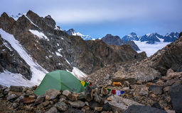 Lonely mountaineers camp in very high snowy moutains beside glacier. Stock Images