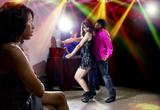Lonely At Nightclub. Single black women jealous of interracial couple on dancefloor Stock Photo