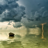 The lonely old boat at the ocean. Comes nearer a thunder-storm with rain and lightning on background Royalty Free Stock Photos