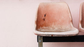 Lonely old chair on pink wall background. Lonely old plastic chair on pink wall background Royalty Free Stock Image