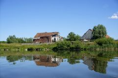 A lonely old house on the lake, the houses reflected in the lake surface of the lake, calm Royalty Free Stock Image