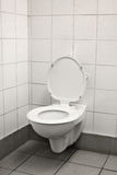 Lonely old loo. White toilet in a white tiled public restroom stock images