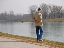 Lonely Old Man. Old man is standing by the lake bank, lake shore Stock Photos