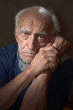 A lonely old man. Portrait of an old man on a black fone.Tired, very lonely old man Stock Photos