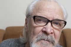 Lonely old man with sore eyes. A lonely sick poor old man suffering from eye diseases, independently engaged in conservative treatment of cataract and glaucoma Royalty Free Stock Photo