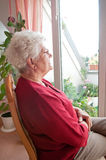 Lonely old woman. Looks out the window Royalty Free Stock Photos
