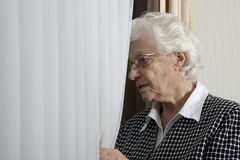 Lonely old woman looking out of window Stock Images