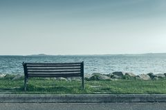 Lonely bench on sea coast royalty free stock image