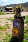 A lonely old yellow hiking boot with flowers on top placed over a stone sign of Camino de Santiago, Navarra, Spain Stock Photos