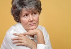 Lonely older woman. In thought on yellow background Royalty Free Stock Photography