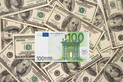 Lonely one hundred euros over. Lonely one hundred euros laying over handreds of dollars Royalty Free Stock Photography