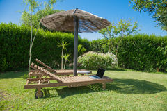 Lonely open laptop on wooden lounge chair Stock Photography